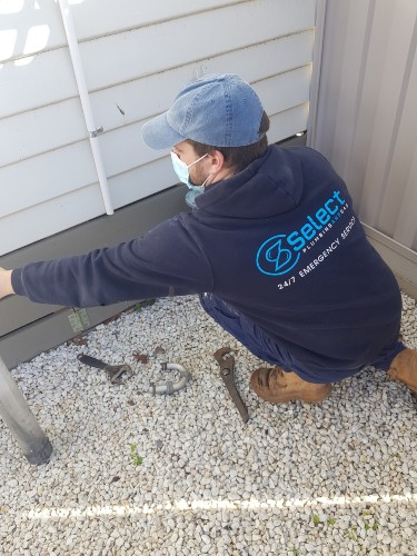 Plumber with mask working on outside drains Moonee Ponds